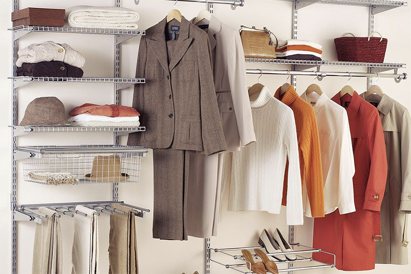 A well-organized closet with several hanging shirts and accessories stacked on white wire organization shelves.