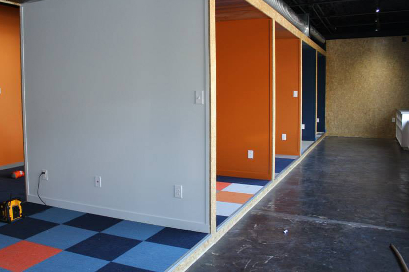 Interior of an office building with blocked off cubicles decorated with orange and blue.