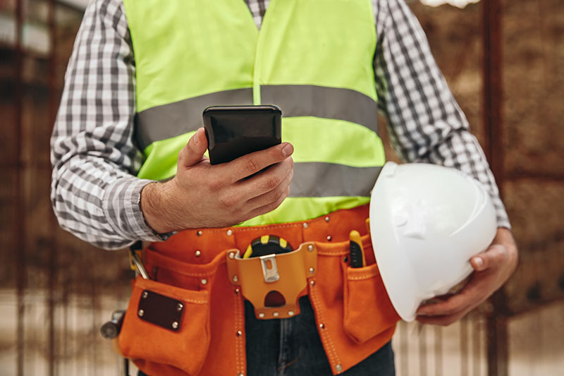 Male construction worker from the neck down wearing yellow safety vest, an orange tool belt, holding a white hard hat and holding a black smartphone.