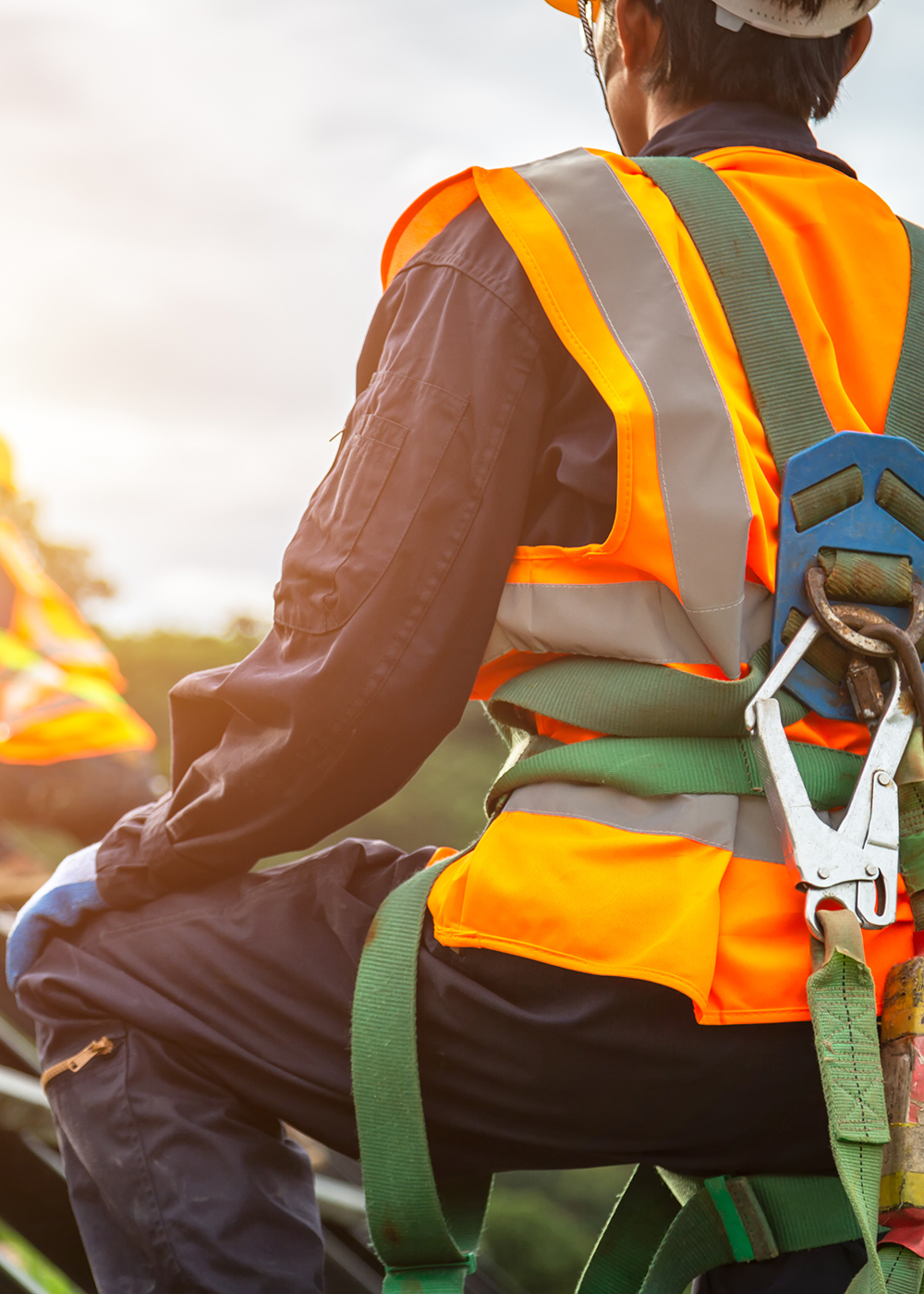 Construction worker in orange safety vest and green harness while on the roof of a building.