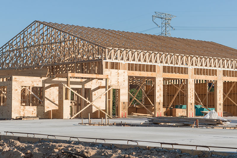Wood frame house under construction with foundation in Humble, Texas, USA. New stick built framing one floor commercial building clear blue sky. Pile of beams, log, sand, gravel. Industrial background