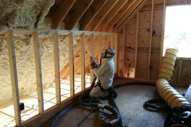Man in white full body suit installing spray foam insulation in an attic.