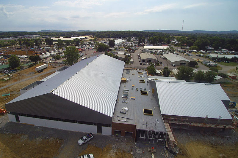 Drone footage of a gray metal building from above.