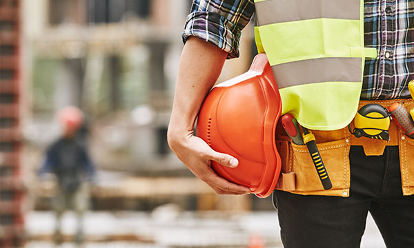 Construction worker. Cropped photo of male professional builder in working uniform with construction tool belt, yellow safety vest, holding a safety helmet while standing outdoor of construction site.