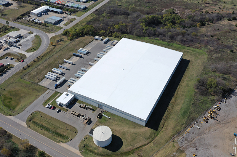 Drone footage of a white metal building from above.