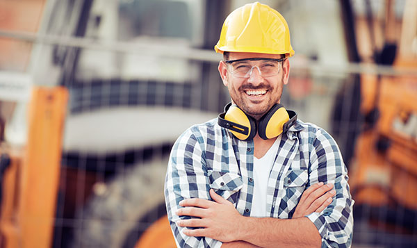 Young male construction worker with construction site behind him.