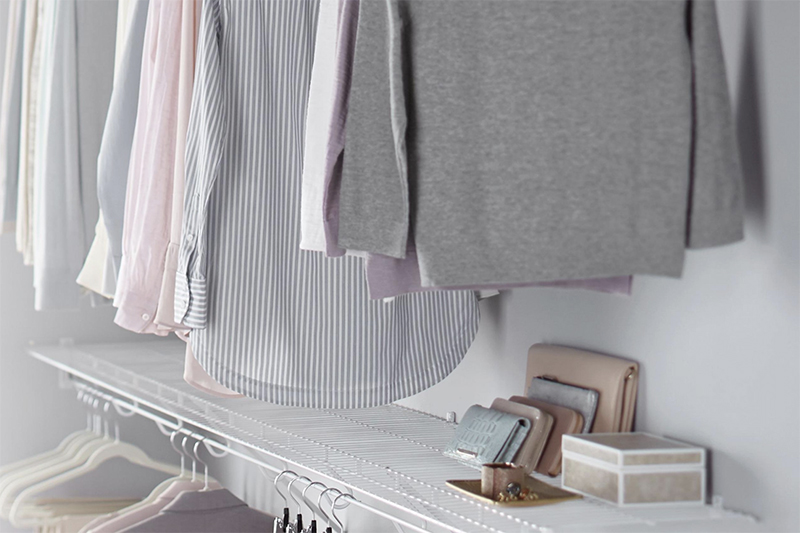 A well-organized closet with several hanging shirts and accessories stacked on a white wire organization shelf.