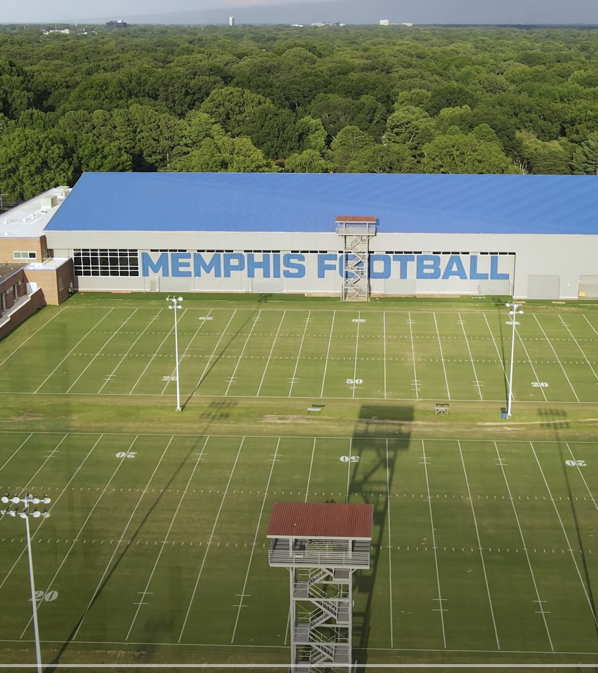 Completed Memphis Football practice facility with blue roof, gray sides, and two practice football fields to the side.