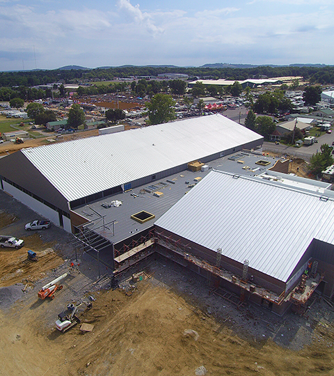 Drone footage of a metal building during its construction.