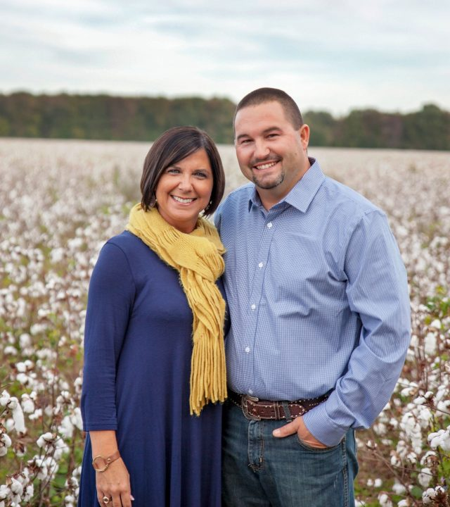Edward and Tiffany Jones standing in a cotton field and smiling at the camera